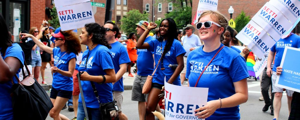 Young Voters wearing blue shirts and holding signs marching in support of Setti Warren